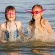 Girls in swimming goggles snorkeling and laughing at sea on a wa — Stock Photo