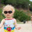 Adorable blonde curly hair little girl in fashionable sunglasses — Stock Photo