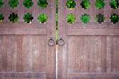 Ancient closed wooden gate with two door knocker rings — Stock Photo