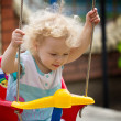 Adorable blonde curly hair little girl having fun on a swing — Stock Photo