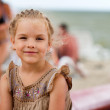 Beautiful girl sitting and smiling on a beach — Stock Photo
