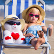 Stock Photo: Child sits on deck chair with toy