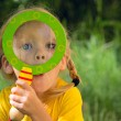 Girl with surprise looks through a magnifying glass — Stock Photo