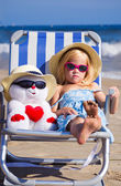 A child sits on a deck chair with a toy — Stock Photo