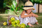 Girl sitting on the grass with a basket of apples — Stock Photo