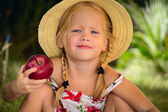 The girl in a hat with red apple — Stock Photo