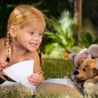 Stock Photo: Girl reading book with toys outdoors