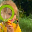 Stock Photo: Girl with surprise looks through magnifying glass