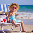 Stock Photo: A child sits on a deck chair with a toy
