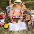 Girl reading a book with toys outdoors — Stock Photo