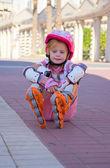 Girl sitting on roller skates — Stock Photo
