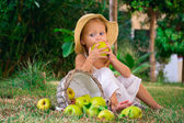 Girl biting an apple on a clearing — Stock Photo