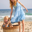 Girls on the beach with a basket — Stock Photo #13963649