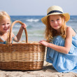 Girls on the beach with a basket — Stock Photo #13963919