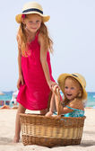 Girls on the beach with a basket — Stock Photo