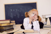 Girl lies with a magnifying glass and books — Stock Photo