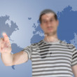 Casual young man standing and pointing on the map — Stock Photo