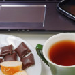 Laptop and cup of hot evaporating tea on table — Stock Photo