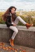 Radostné bruneta dívka sedí a směje se — Stock fotografie