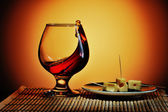 Glass of cognac with cheese plate — Stock Photo