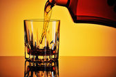 Pouring whisky into a glass — Stockfoto