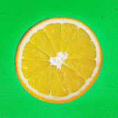 Slice of orange on green drop background — Stock Photo