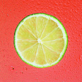 Slice of lime with drop on red background — Stock Photo