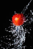 Red apple water splash on black background — Stock Photo