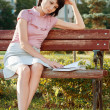 Young woman reading book sitting on the bench — Stock Photo