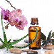 Herb leaf and Orchid flowers with an aromatherapy essential oil glass bottle — Stock Photo