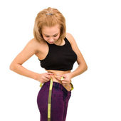 Beautiful young woman measuring her waist — Stock Photo