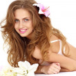 Woman with flowers lies against white background - Photo
