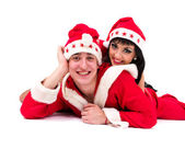 Happy young couple wearing santa claus clothes — Stock Photo