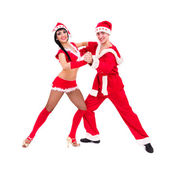 Happy young couple wearing santa claus clothes dancing — Stock Photo