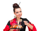 Woman wearing a traditional red dress eating sushi — Stock Photo