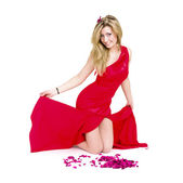 Sexy woman in red dress with rose petals — Stock Photo