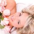 Woman with rose  lying on towel - Stock Photo