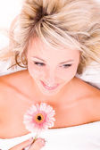 Woman with flower lying on towel — Stock Photo