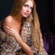 Woman wearing a fur coat posing — Stock Photo
