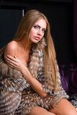 Woman wearing a fur coat posing — Stock Photo