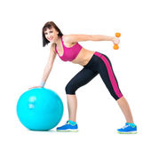 Young woman exercising with dumbbells on a fitness ball — Stock fotografie