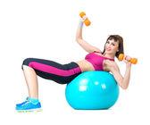 Genç bir kadın fitness topu üzerinde döşeme dumbbells ile egzersiz — Stok fotoğraf