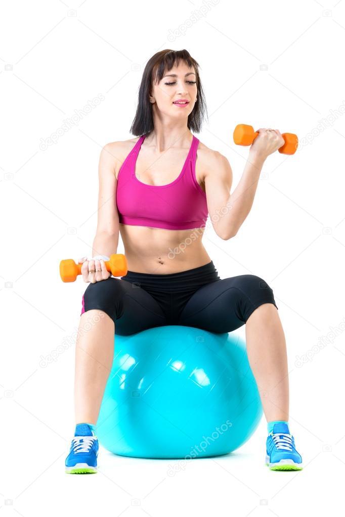 用哑铃在健身球锻炼的年轻女子