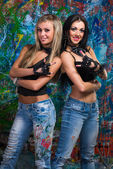 Two young girls stands near wall with graffiti — Stock fotografie