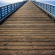 Long wooden Pier before blue sky — Stock Photo