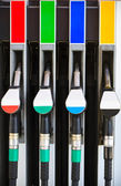 Gasoline pump nozzles at petrol station — Stock Photo