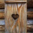Stock Photo: Window shutter with heart of a wooden log cabin in the European