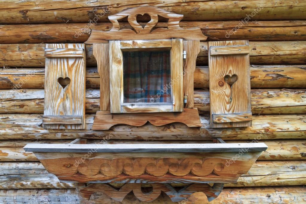 finestra con persiane di cuore di una casetta in legno in