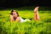 Beautiful sexy girl lying in grass — Stock Photo