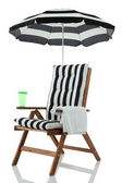 Beach chair with umbrella, towel and drink — Stock Photo